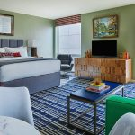 The Graduate Madison Liberty suite has a large bed with two side tables, a couch with a coffee table, a large television and is flooded with sunlight